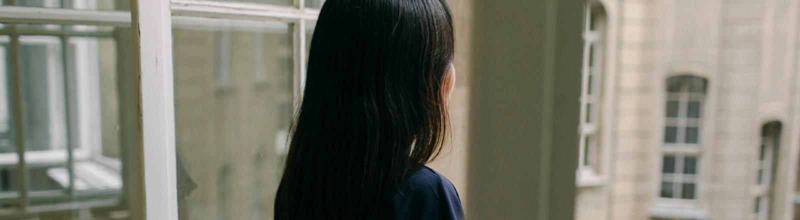 Eine Frau steht an einem Fenster.