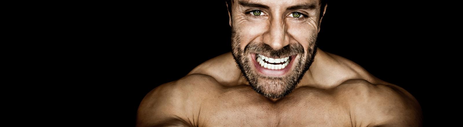 Ein sehr muskulöser Mann schaut grimmig in die Kamera.