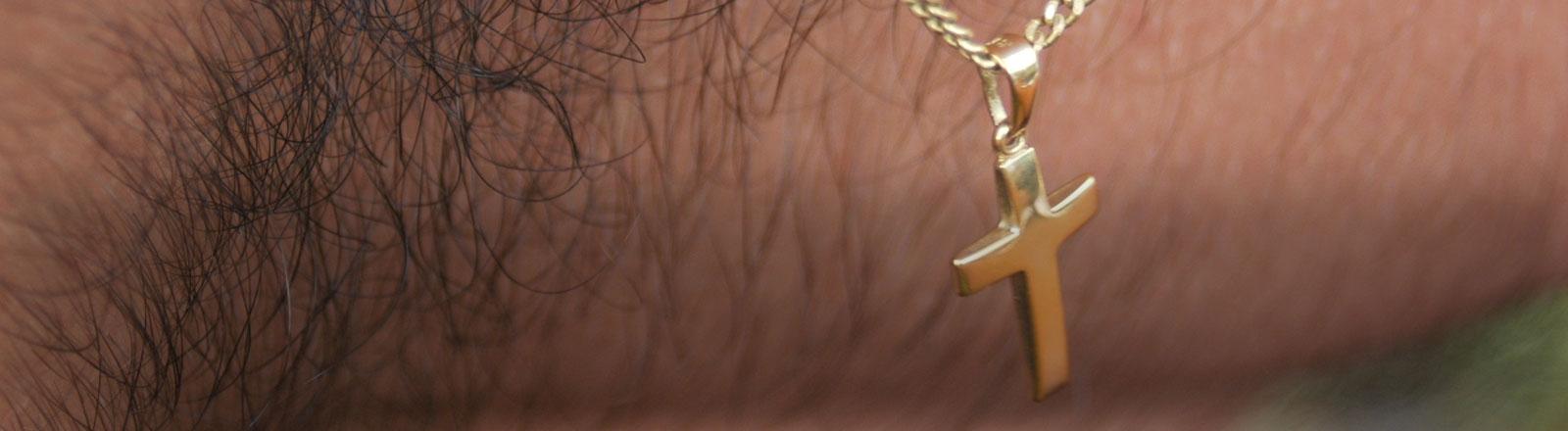Ein Kreuz auf einer behaarten Männerbrust.