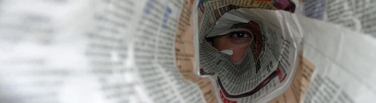 Ein Mann schaut durch eine zusammengerollte Zeitung.