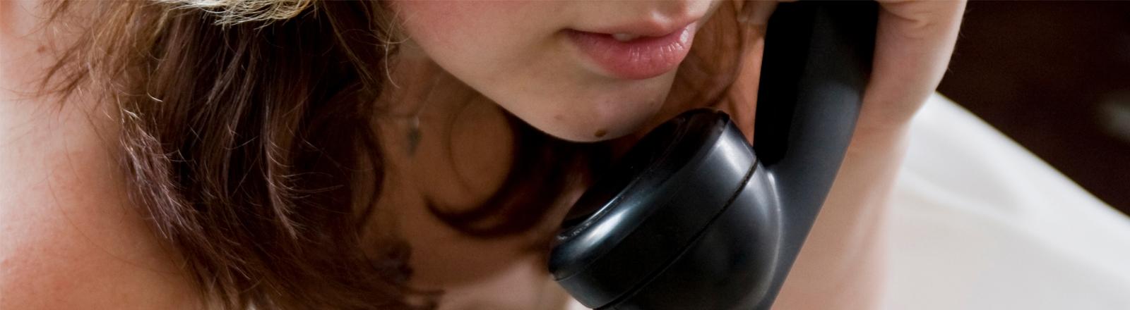 Eine Frau liegt im Bett und telefoniert mit einem alten Telefon.