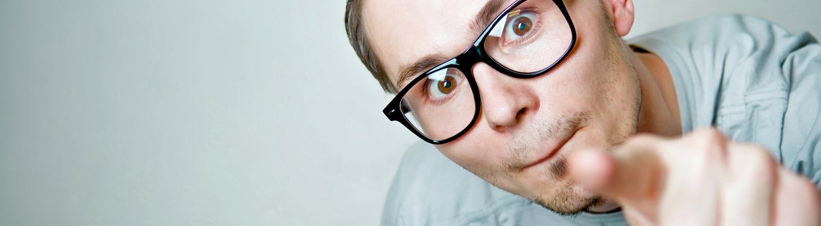 Ein Typ mit Nerd-Brille zeigt auf den Betrachter des Bildes.