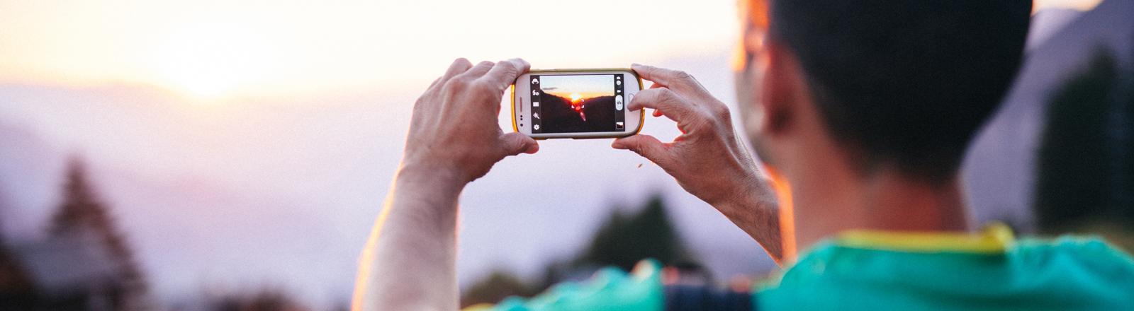 Mann, der ein Photo mit dem Handy macht.