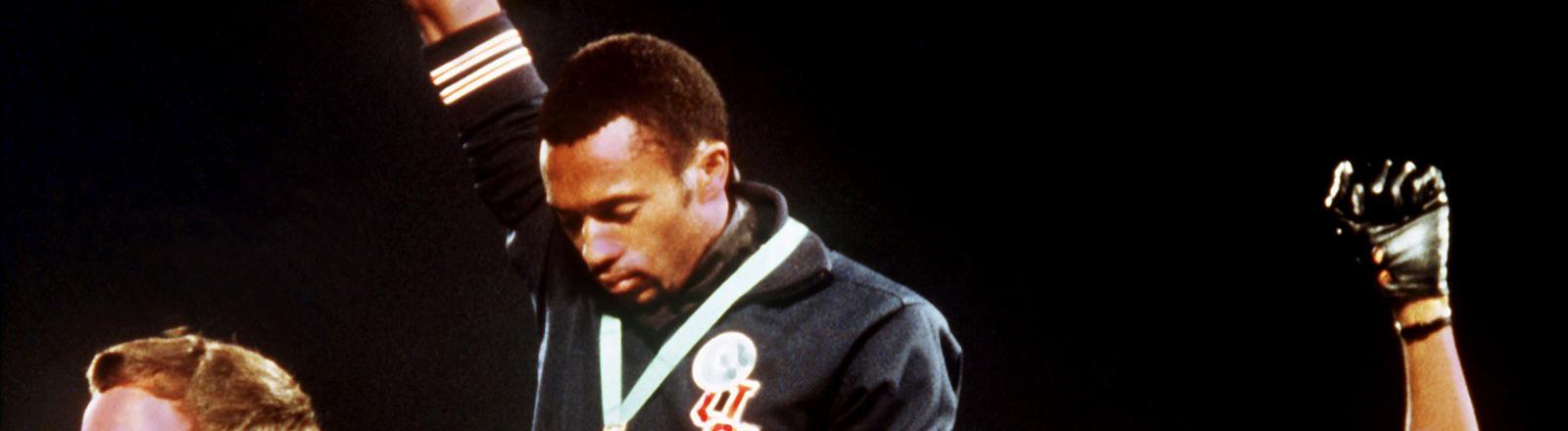 ´Die US-amerikanischen Sprinter Tommy Smith und John Carlos protestieren mit einer zum Himmel gereckten schwarzen Faust bei den Olympischen Spielen 1968.