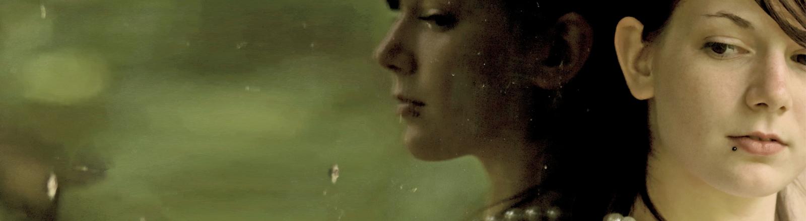 Eine Frau schaut nachdenklich drein und spiegelt sich in einem Fenster.