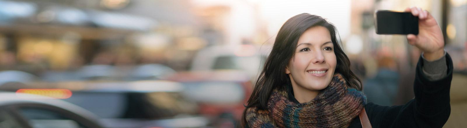 Eine Frau hält ein Smartphone in die Luft