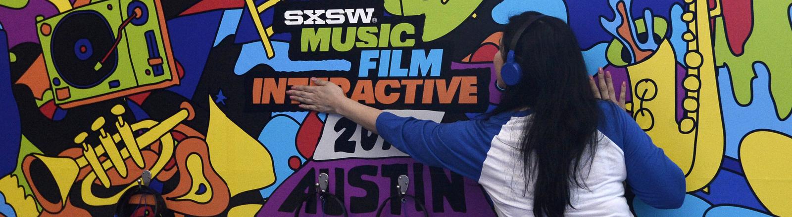 Eine Frau mit Kopfhörern klebt ein Plakat für die SXSW 2016.