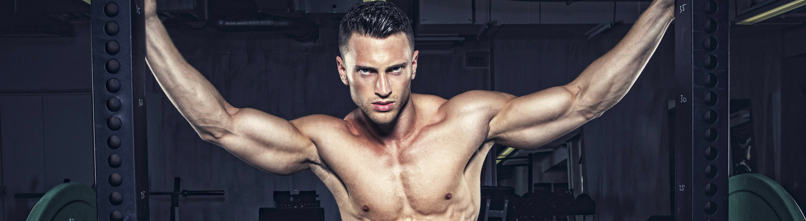 Ein durchtrainierter Mann zeigt seine Muskeln.