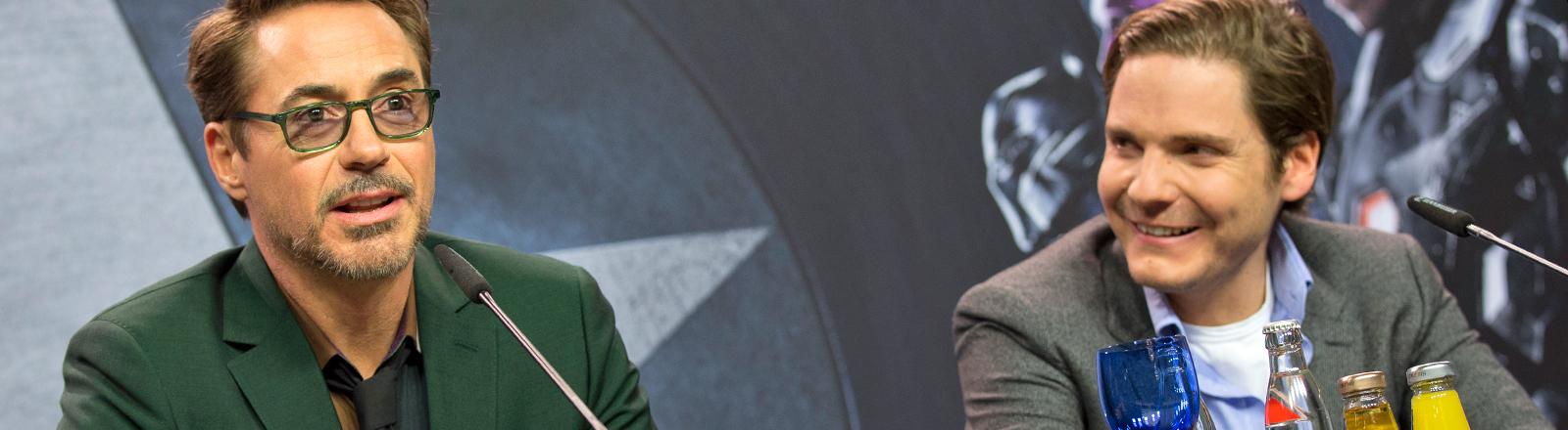 """Robert Downey Jr. und Daniel Brühl auf einer Pressekonferenz zu  """"The First Avenger""""."""