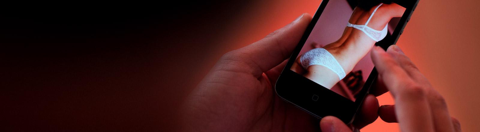 Ein Bild einer leicht bekleideten Frau auf einem Smartphone