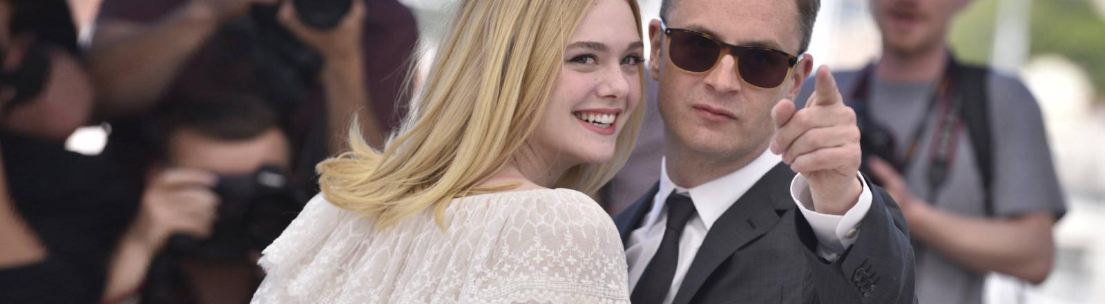 Elle Fanning steht neben Regisseur Nicolas Winding Refn.