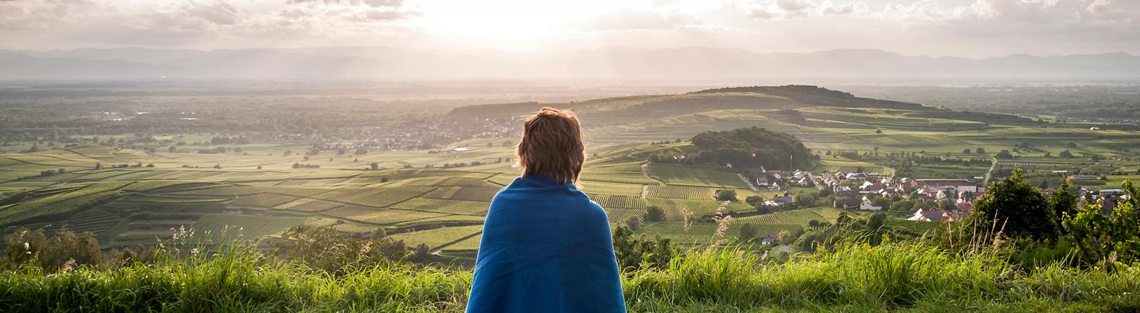 Frau sitzt auf einer Bank vor Panorama.