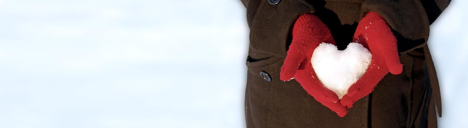 Ein Herz aus Schnee, gehalten von zwei Händen in roten Handschuhen