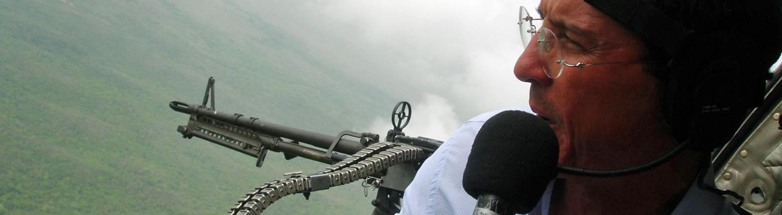 Ein Journalist sitzt in einem Hubschrauber über einem Krisengebiet in Kolumbien (2008). Er spricht in eine Mikrofon.