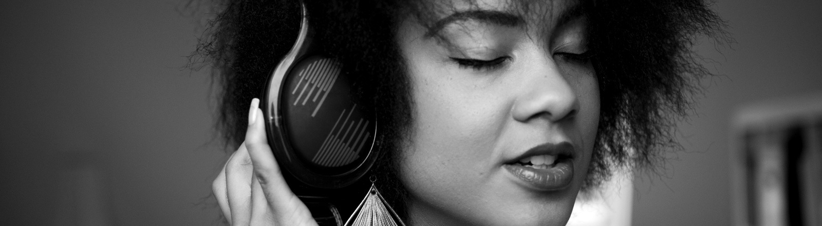 Frau hört mit Kopfhörer