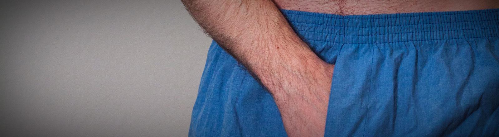 Mann greift sich in Unterhose.