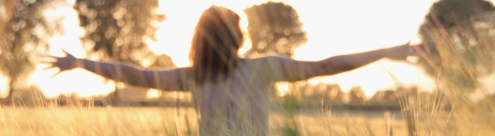 Frau im Sommer auf einer Wiese im Sonnenuntergang