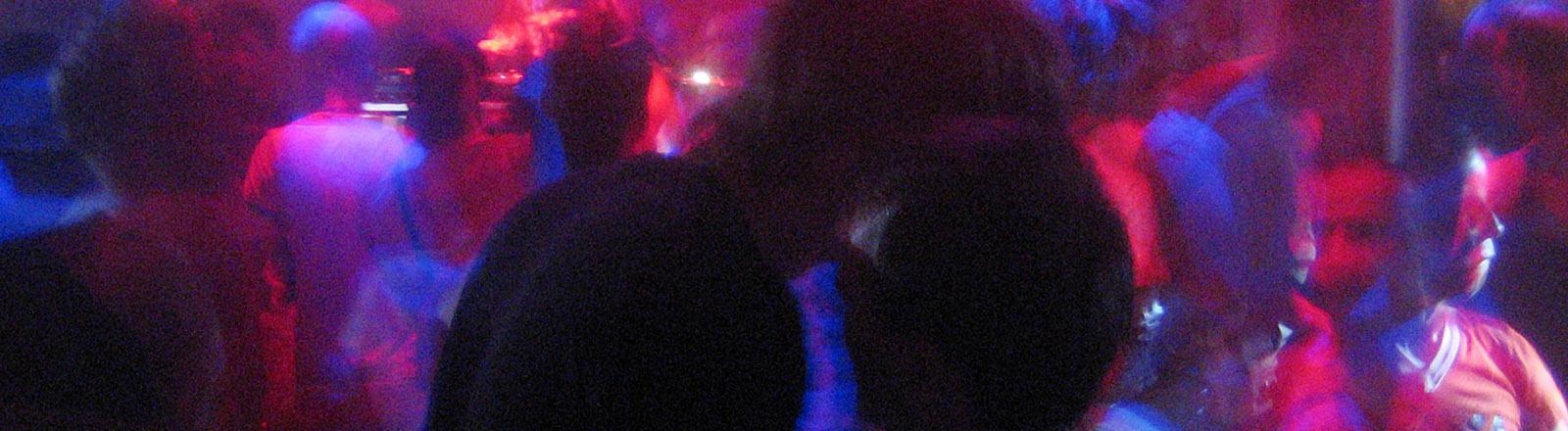 Ein Paar küsst sich auf der Tanzfläche in einem Club.
