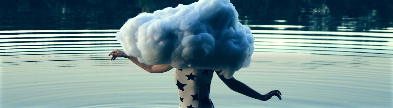 Eine Frau steht im Wasser mit dem Kopf in den Wolken.