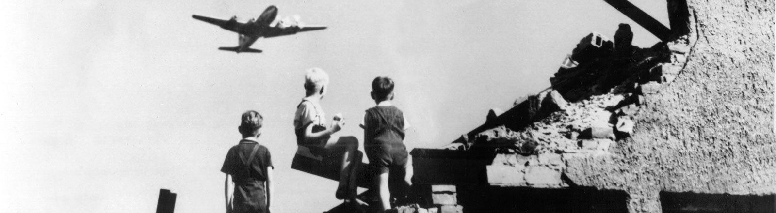 Drei West-Berliner Jungen, die auf einem Trümmerberg spielen, schauen zu einem US-amerikanisches Transportflugzeug vom Typ C-54 empor, das Versorgungsgüter nach West-Berlin bringt (Aufnahme von 1948). Als Reaktion auf die Währungsreform in den Westsektoren am 23.6.1948 verhängte die UdSSR am 24.6.1948 eine Blockade über Berlin. Alle Land- und Wasserwege wurden für den Personen- und Güterverkehr zwischen West-Berlin und Westdeutschland gesperrt. Die Versorgung der Westberliner Bevölkerung und der westalliierten Besatzung erfolgte daraufhin durch eine von den USA und Großbritannien errichtete Luftbrücke.