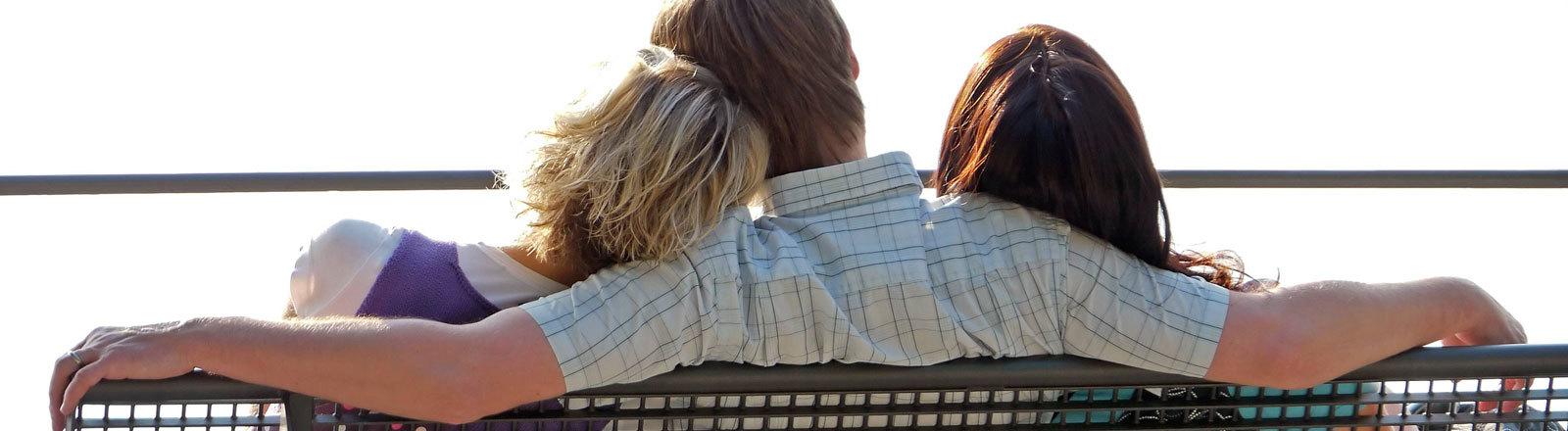 Ein Mann und zwei Frauen sitzen auf einer Bank