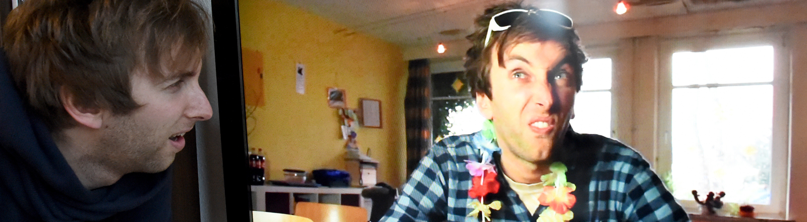 Torge Oelrich (Freshtorge) steht in seiner Wohnung in Wesselburen (Schleswig-Holstein) neben einem Fernseher, auf dem einer seiner Filme läuft.