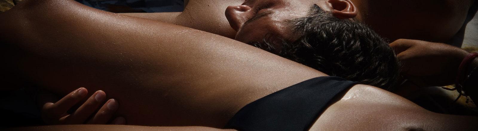 Mann und Frau liegen nackt nebeneinander.