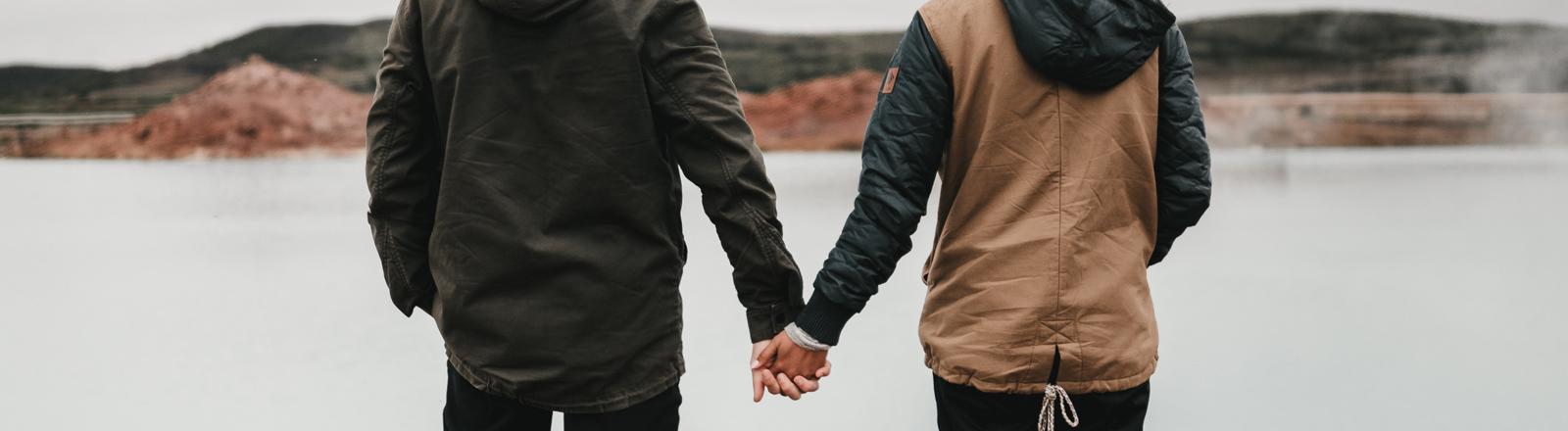 Paar steht an See und hält Händchen
