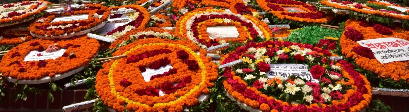 Blumenkränze liegen vor dem Jatiyo-Sriti-Shoudho-Denkmal in Bangladesh, das an die verstorbenen Soldaten des Unabhängigkeitskrieges 1971 erinnern soll.