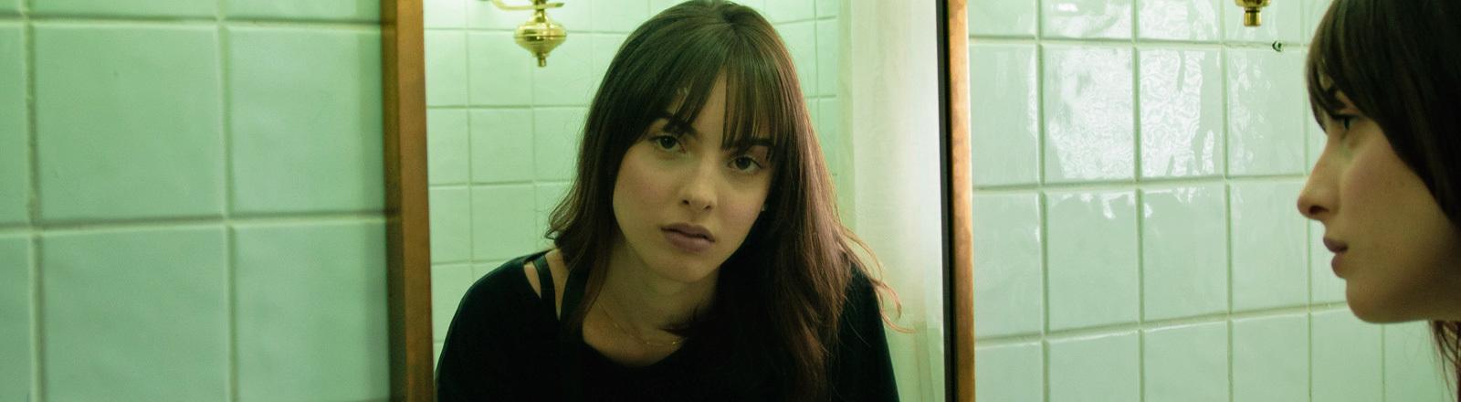 Eine Frau guckt in den Spiegel. Das Spiegelbild schaut gleichgültig.