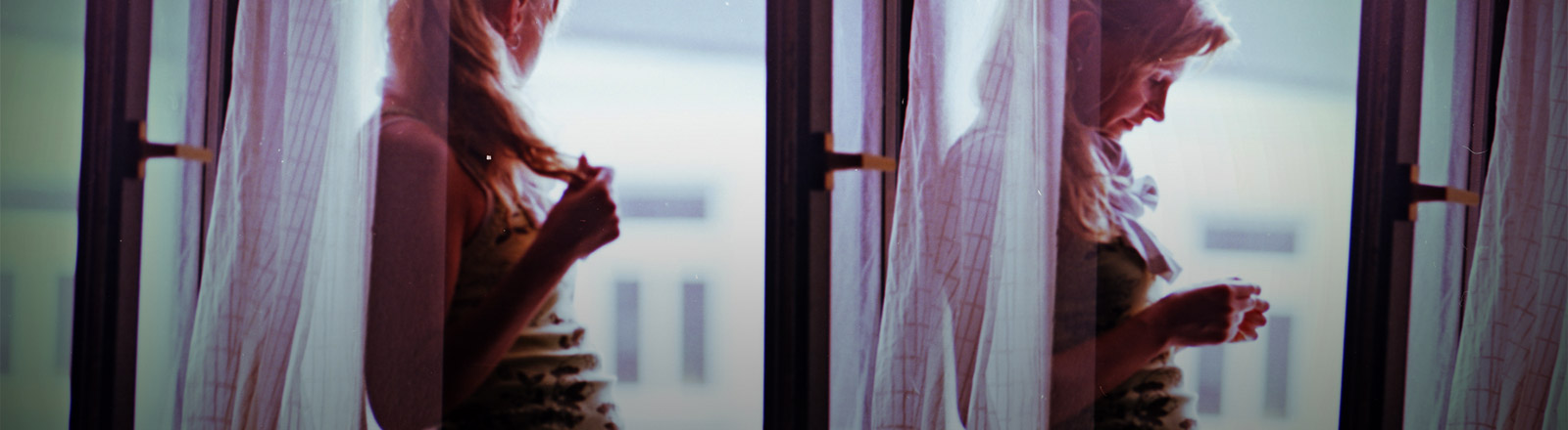 Eine traurige Frau steht an einem offenen Fenster.