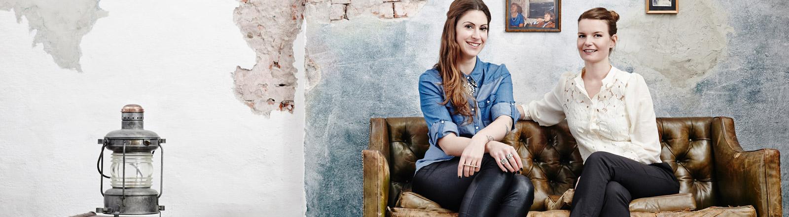 Madita van Hülsen und Anemone Zeim sitzen auf einem Sofa.