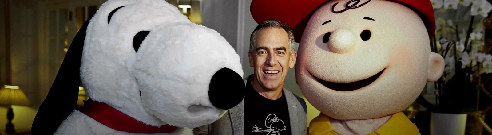 Regisseur Steve Martino mit den Figuren Snoopy und Charlie Brown