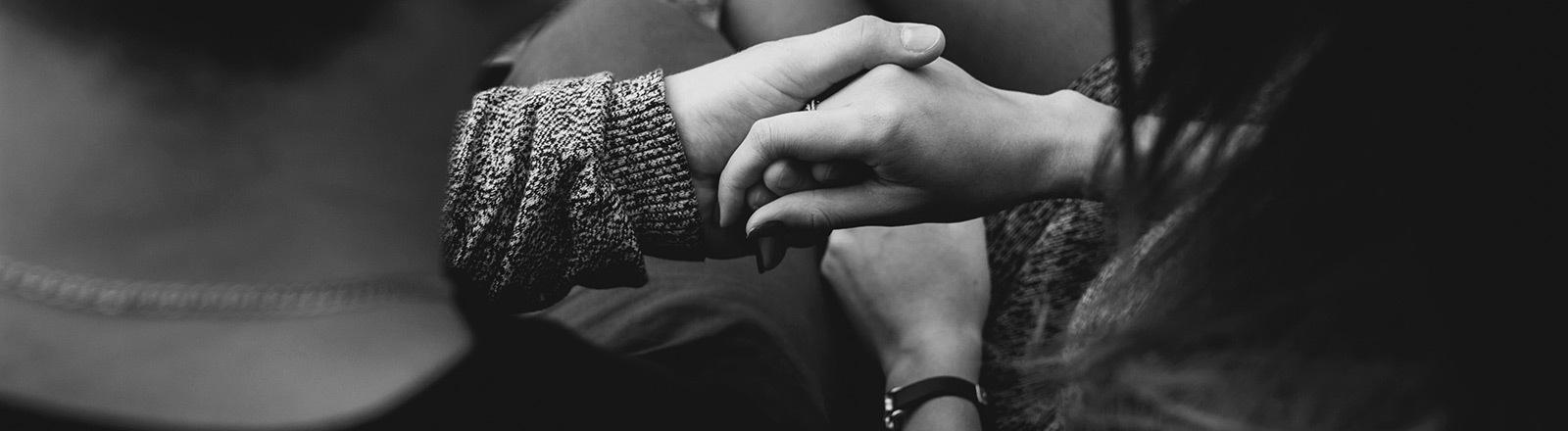 Ein Mann und eine Frau halten ihre Hände