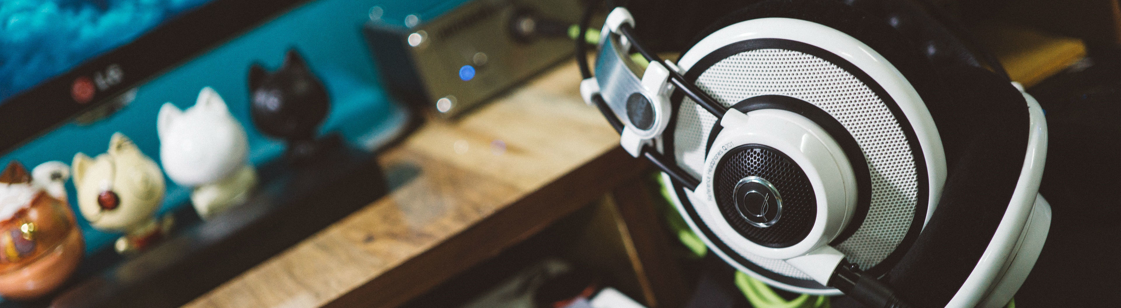 Kopfhörer neben einer Tastatur und einem Bildschirm.