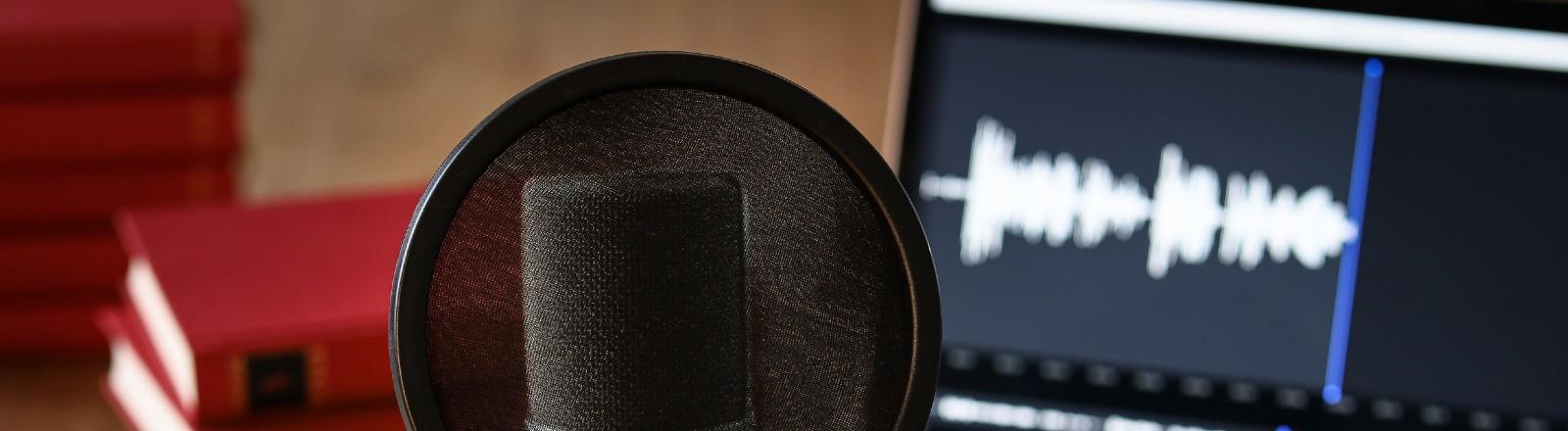 Podcastequipment: Mikrophon, Laptop, ein Buch.