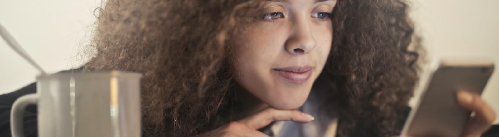 Eine Frau schaut sehnsuchtsvoll ins Handy.