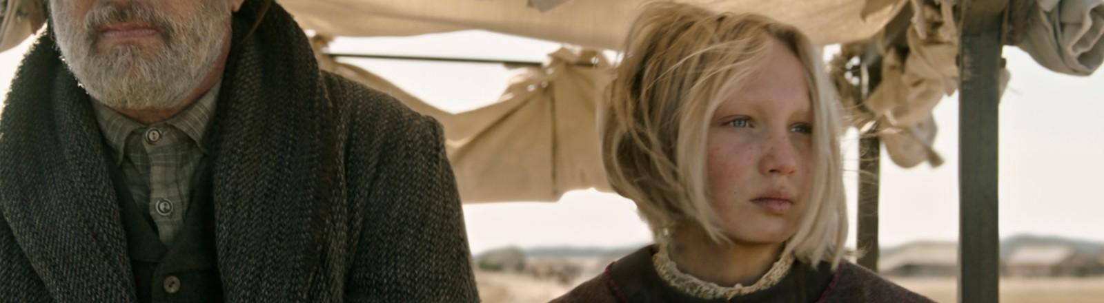 """Helena Zengel neben Tom Hanks auf einer Kutsche im Film """"Neues aus der Welt""""."""