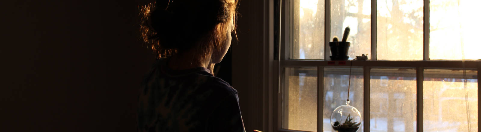 Frau guckt aus Fenster