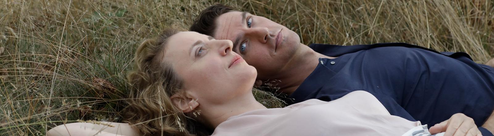 """Filmstill aus """"Ich bin dein Mensch"""": Alma (Maren Eggert) und der Androide Tom (Dan Stevens) liegen gemeinsam auf einer Wiese."""