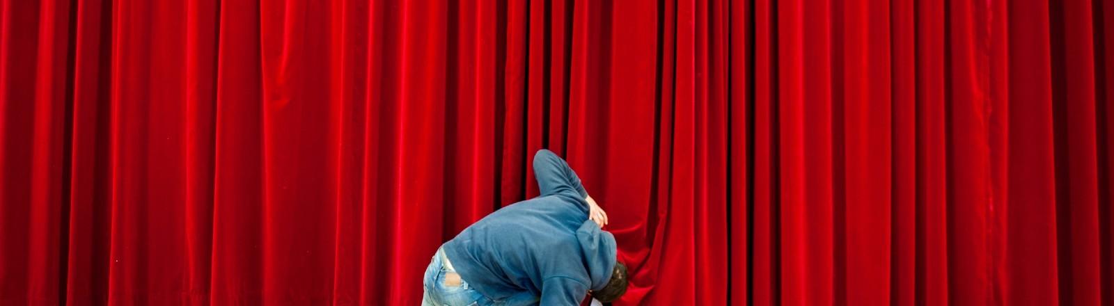 Mann blickt neugierig unter den Kino-Vorhang