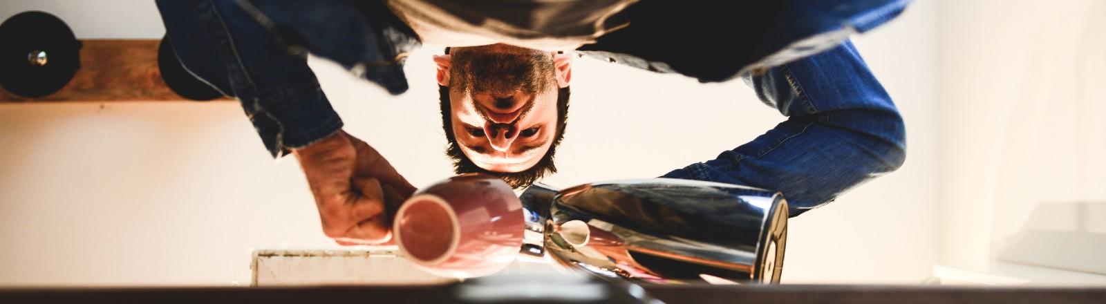 Von unten betrachtet: Ein Mann schüttet sich eine Tasse Kaffee ein.