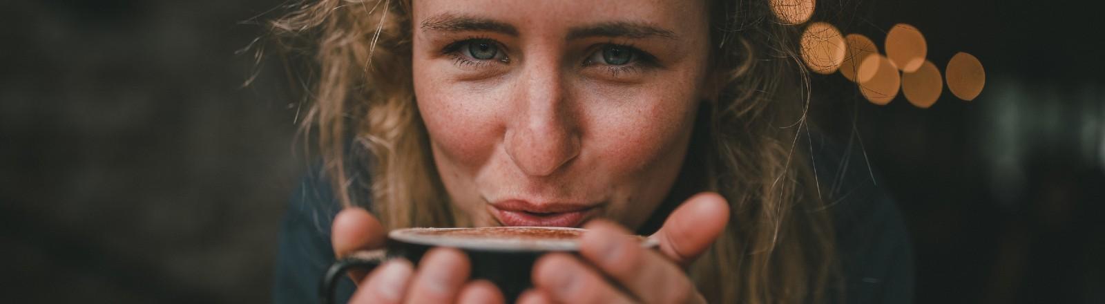 Eine Frau hält eine Tasse Kaffee in der Hand - ein Moment voller Genuss.