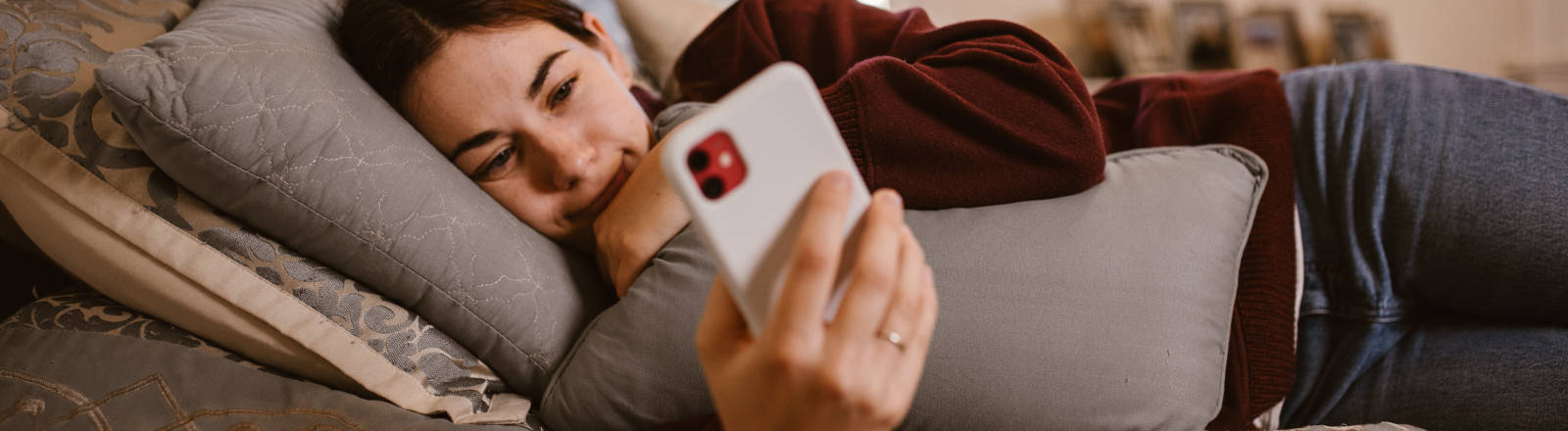 Eine Frau liegt mit Smartphone in der Hand im Bett