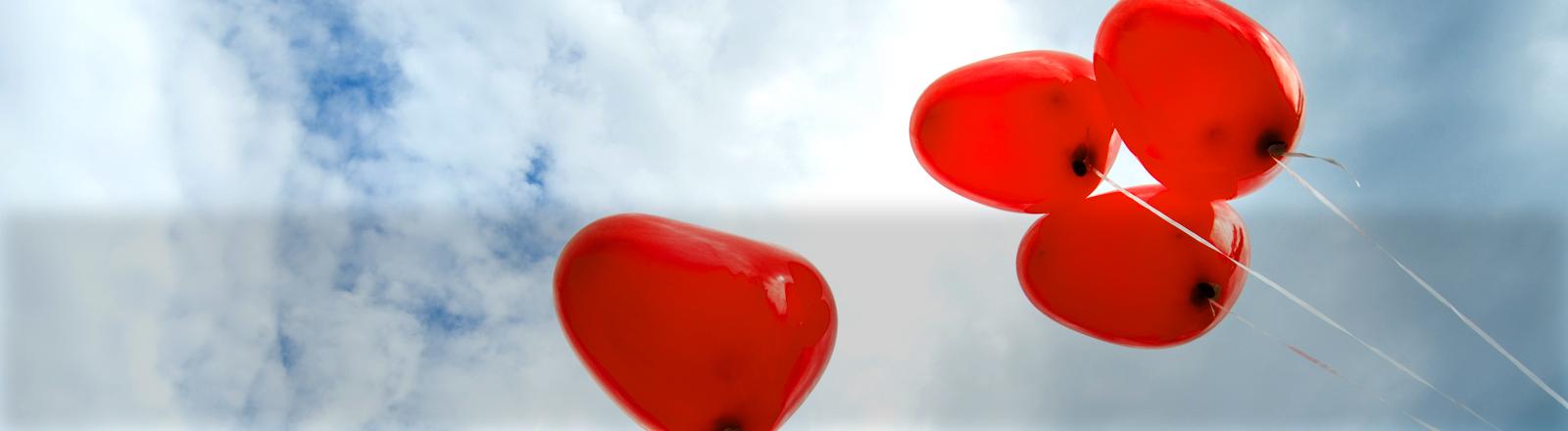 Mehrere Herzluftballons fliegen vor blauem Himmel.