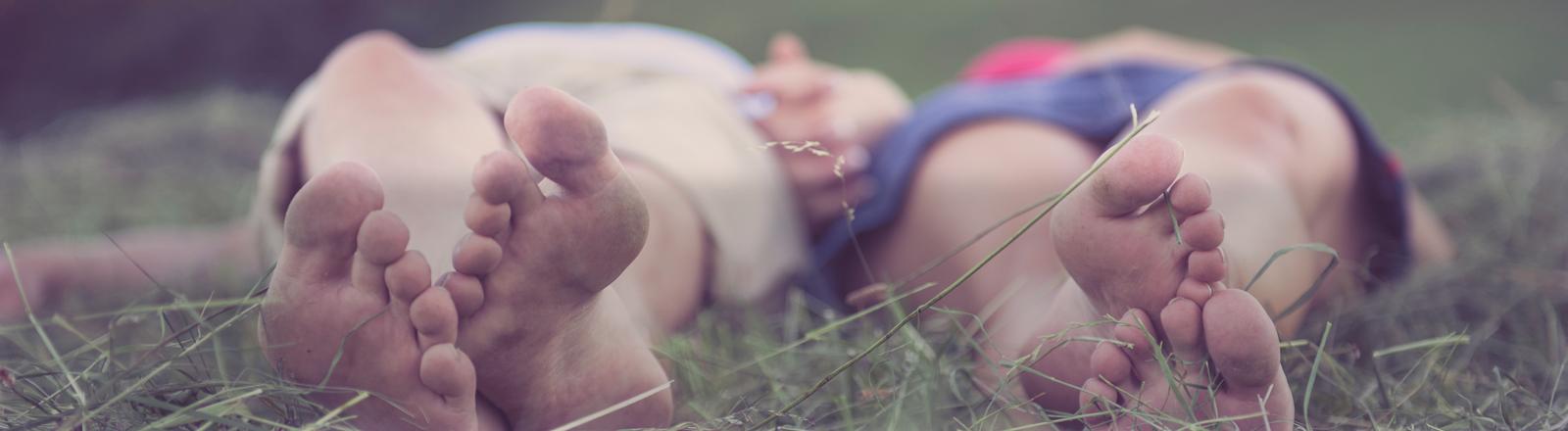 Zwei Menschen liegen im Gras und halten sich an den Händen.