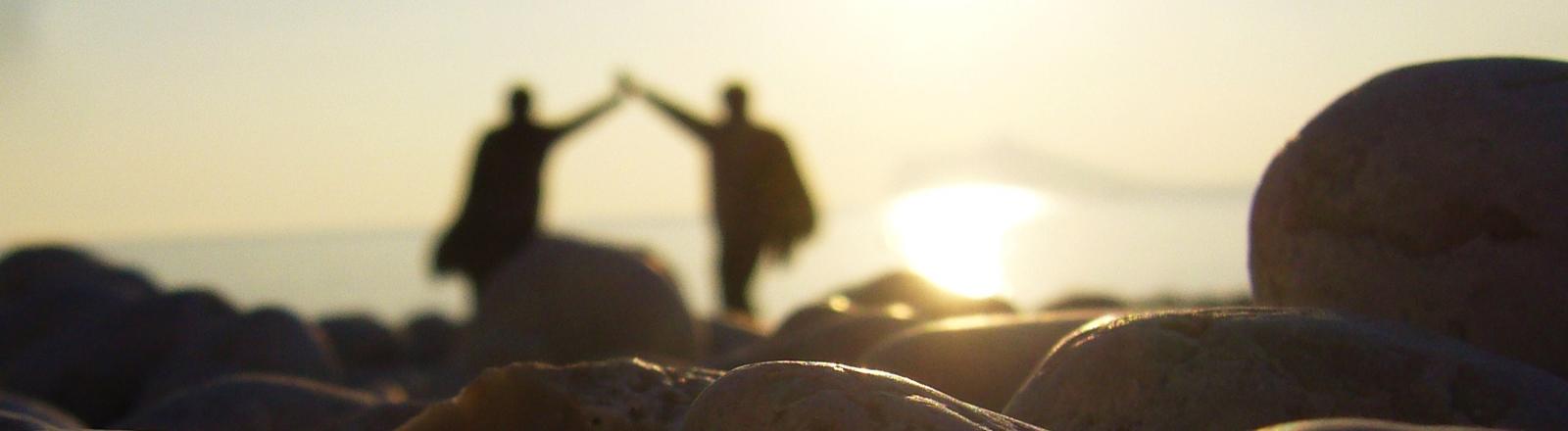 Zwei Menschen gehen mit nach oben ineinander verschränkten Armen in die Sonne.