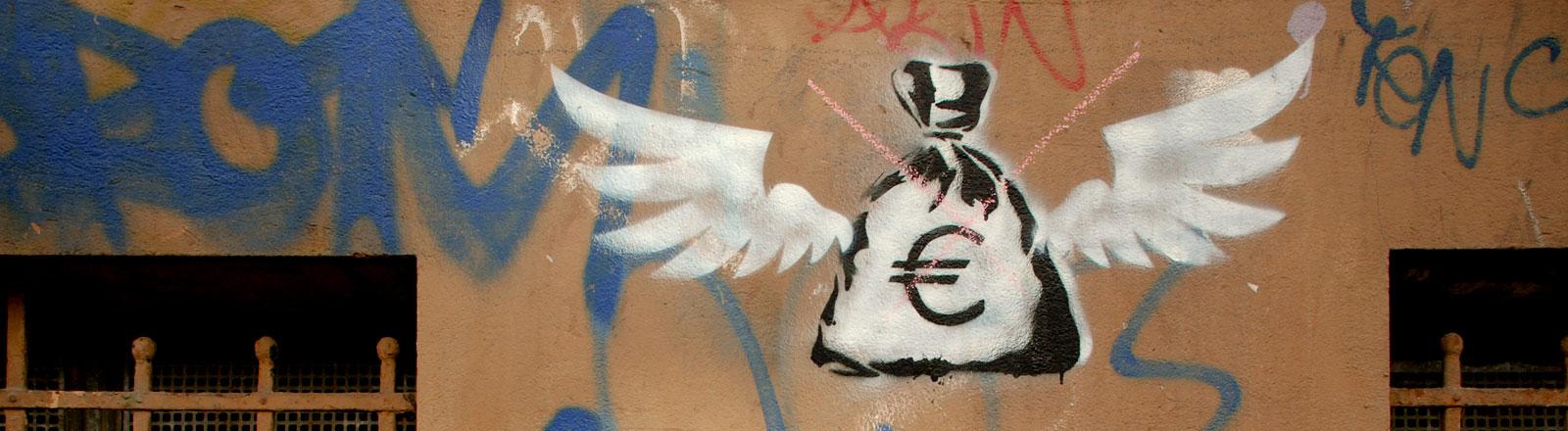 Ein Graffitti auf einer Wand zeigt einen Geldsack mit Flügeln.