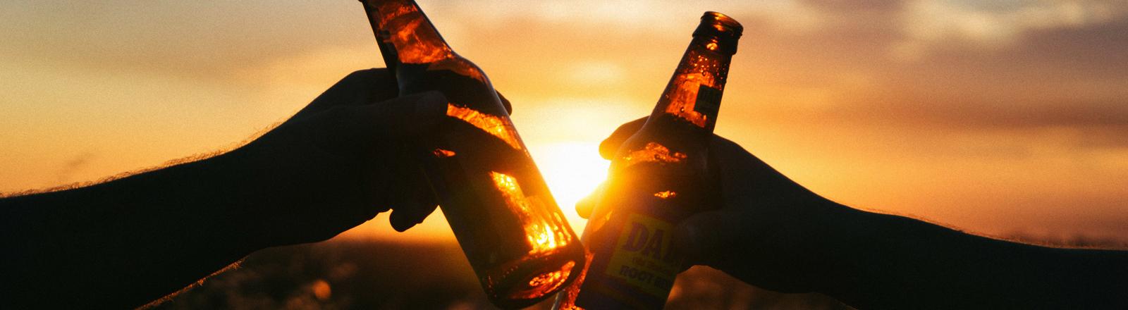 Anstoßen mit Bierflaschen.