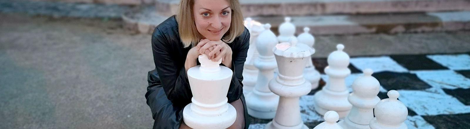Elisabeth Pähtz vor einem Schachbrett.